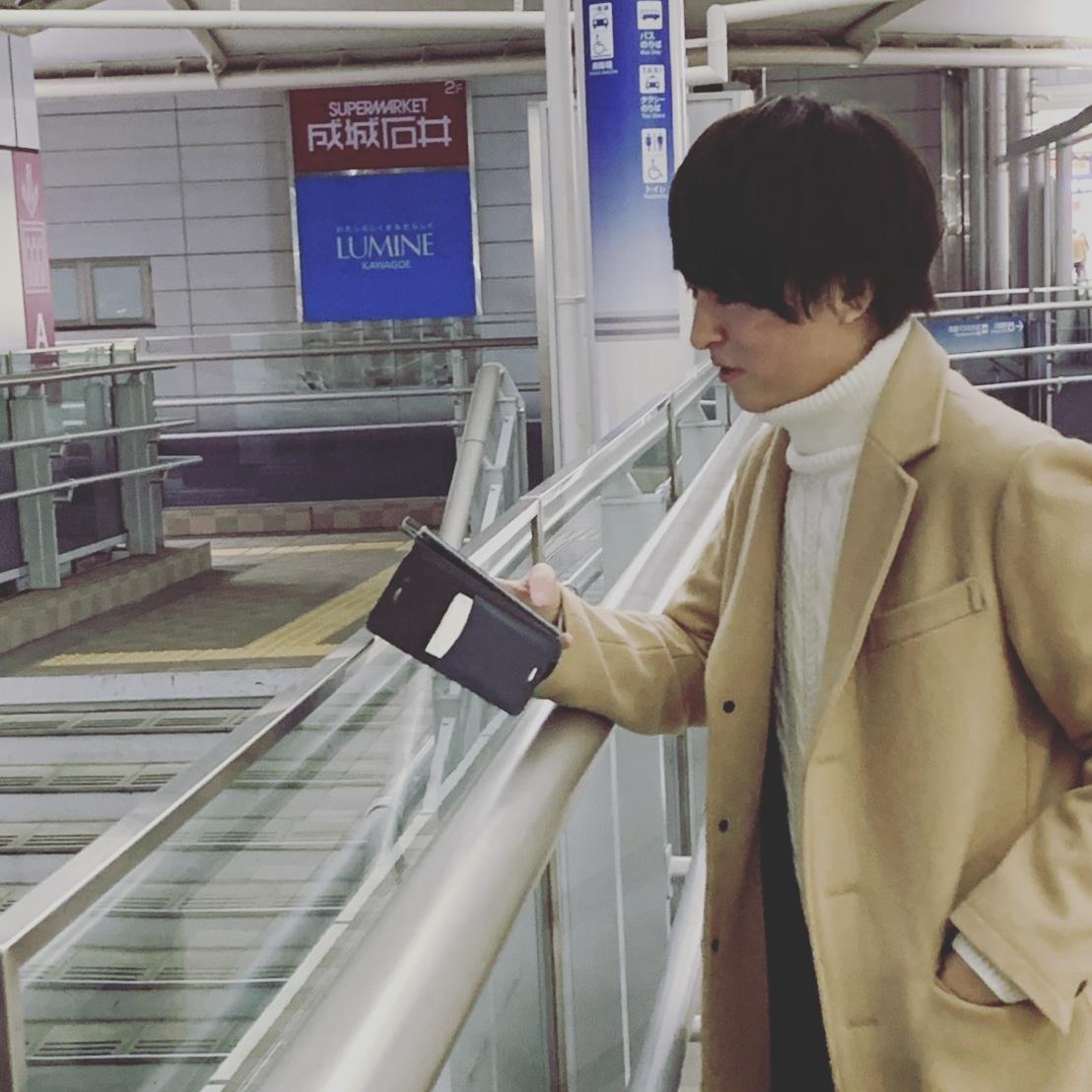 駅で携帯を見る岸大貴