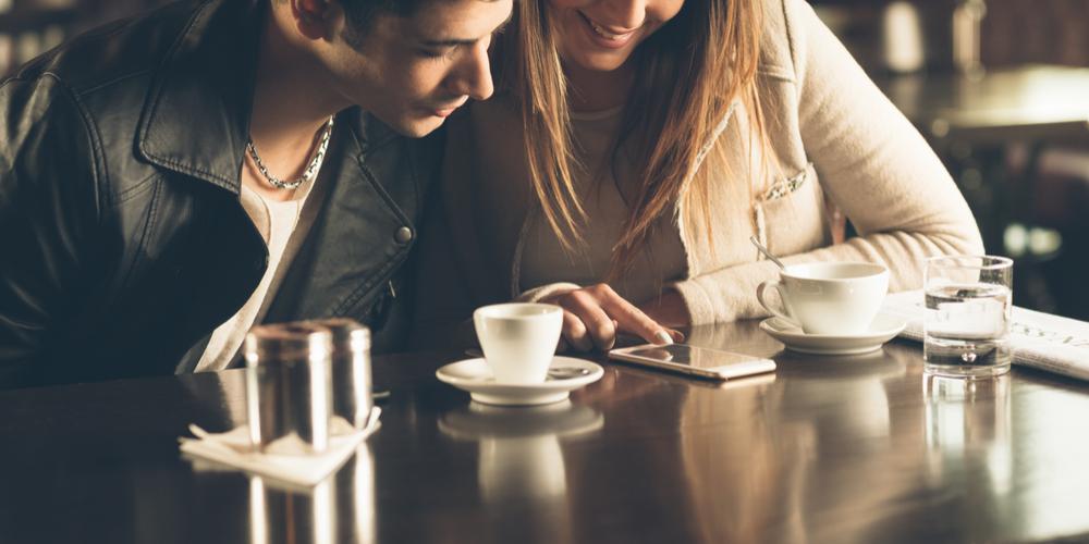 机に置いたスマートフォンを見る男女