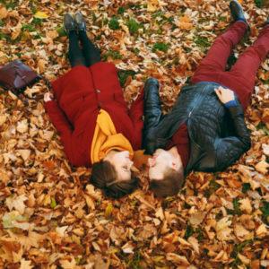 落ち葉の上で寝転んで手をつなぐ男女