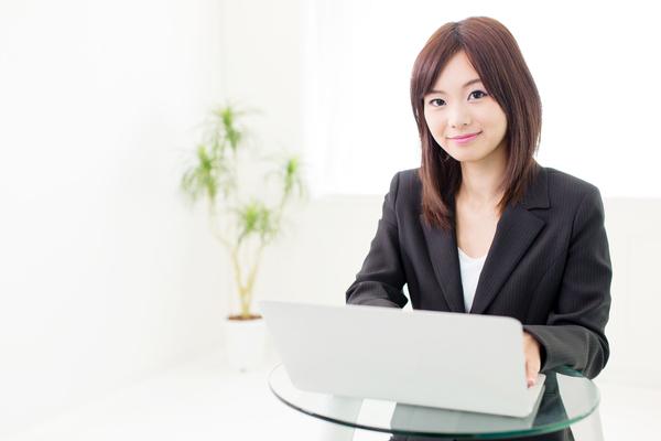 パソコンを触りながらこちらを見るスーツの女性