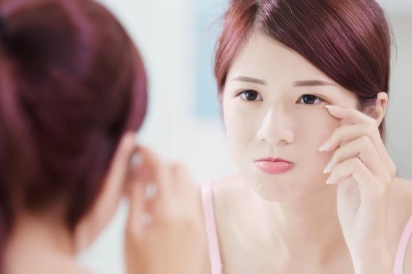 鏡で顔色を見る女性