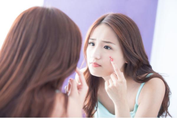 鏡で吹き出物をチェックする女性