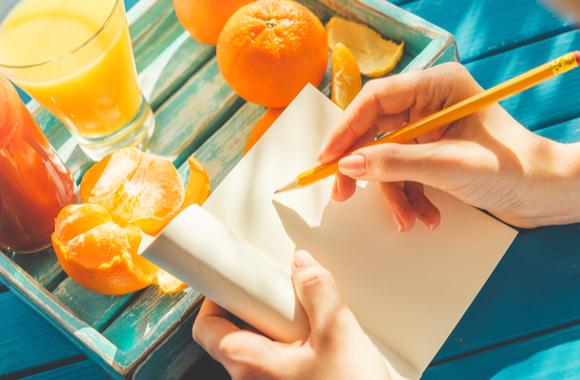 オレンジとノートにペンで書き込む手