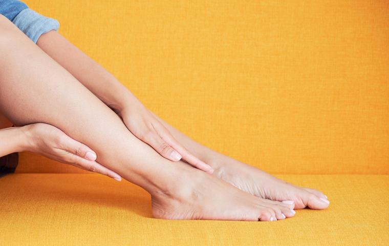 脚を擦る女性