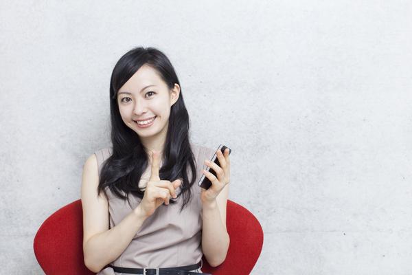 スマートフォンを持って笑う女性