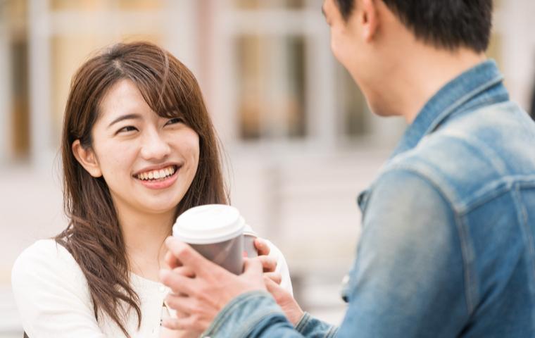 コーヒーを持つ男女