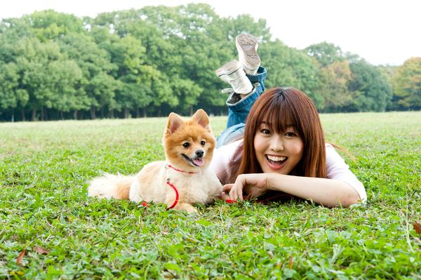 芝生に寝転ぶ女性と犬