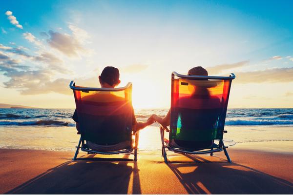 夕日のビーチで座るカップル