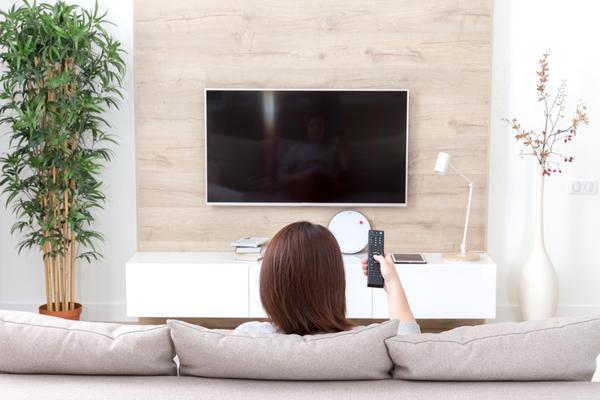 テレビのリモコンを動かす女性