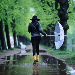 濡れた道を傘を持って歩く人