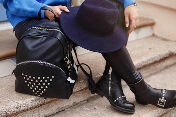 階段に座ってハットを持つブーツの女性