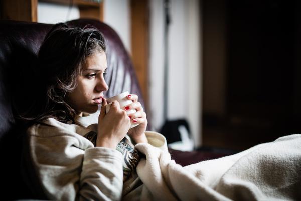カップを手に持ち毛布にくるまる女性