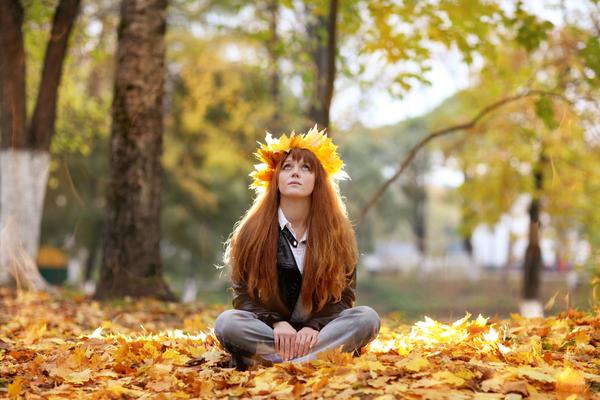 落ち葉の中に座る女性