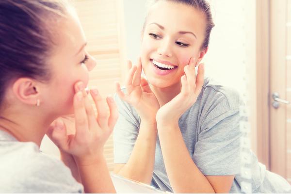 鏡を見ながらほほ笑む女性