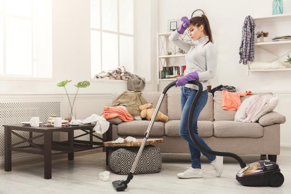 部屋に掃除機をかける女性