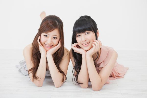 頬杖をついて笑う女性2人